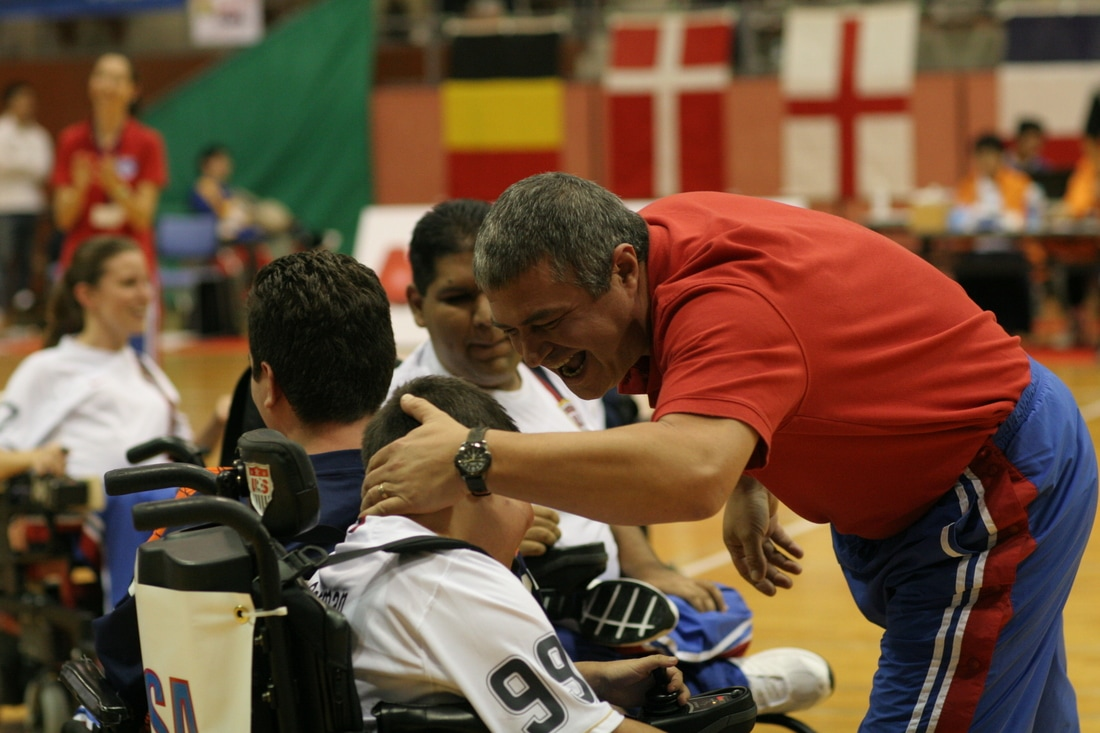 Image of a coach patting an athlete on the head