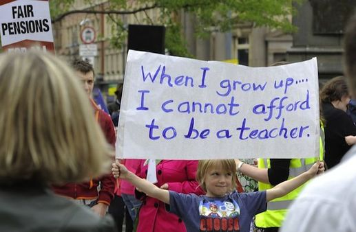 Image of a crowd at a rally to support teachers with the focus on a young girl holding up a sign that reads: